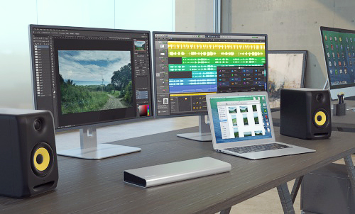 Image of the Thunderbolt 2 Dual-Video Dock deployed in a creative studio, and connected to digital optical audio speakers
