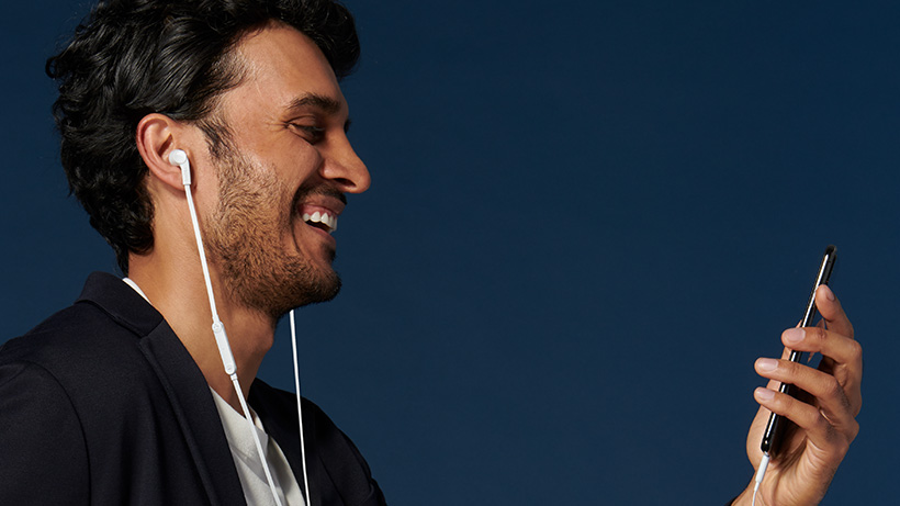 Man laughing while looking at his iPhone, with headphones in his ears