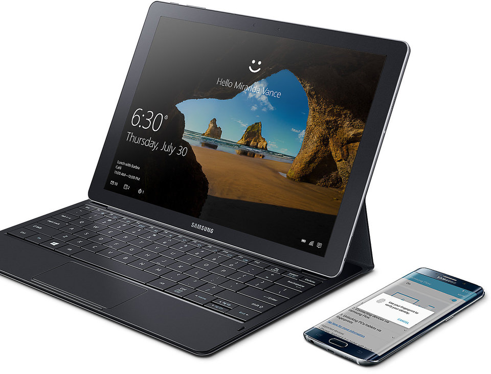 Galaxy TabPro S is propped up with keyboard attached and Galaxy smartphone is next to it